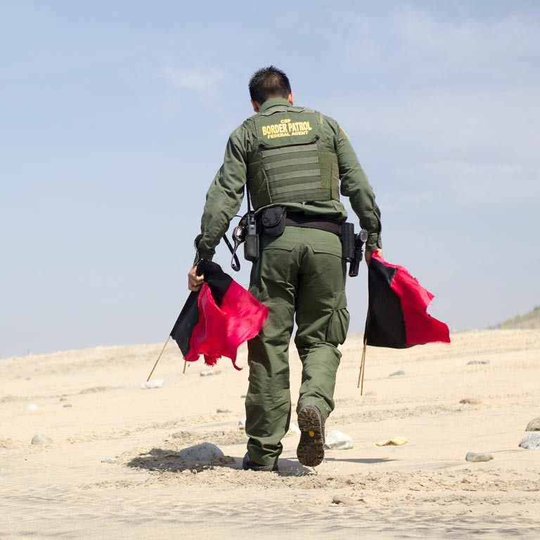 Border Patrol Federal Agent carrying red flags