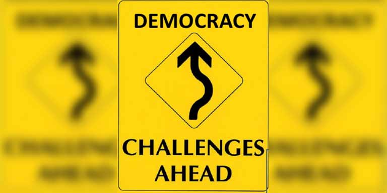 yellow traffic sign that says democracy challenges ahead