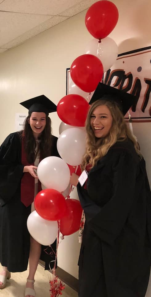 Two female students wearing black graduation gowns with red balloons