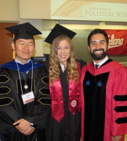 2 male and 1 female graduates wearing graduation gowns
