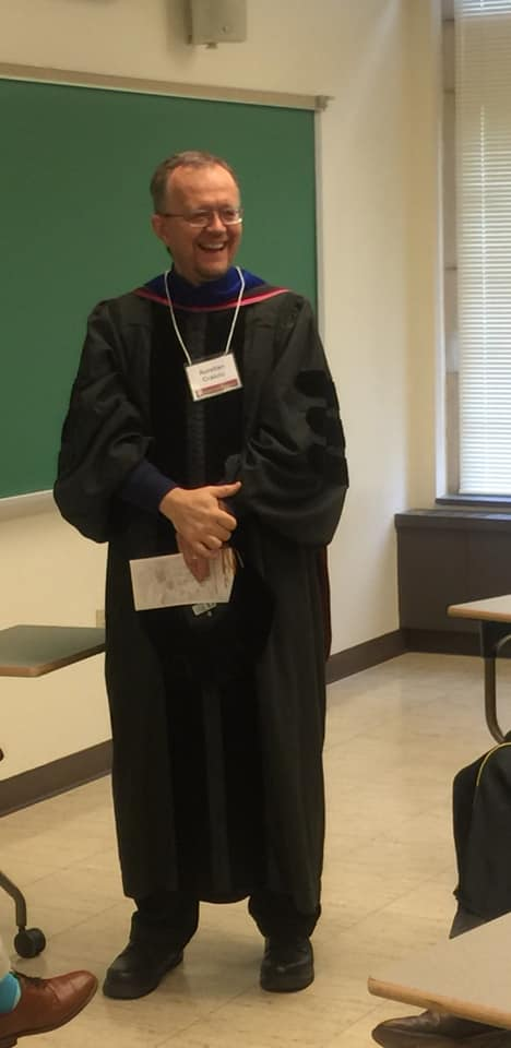 faculty member in graduation gown laughing