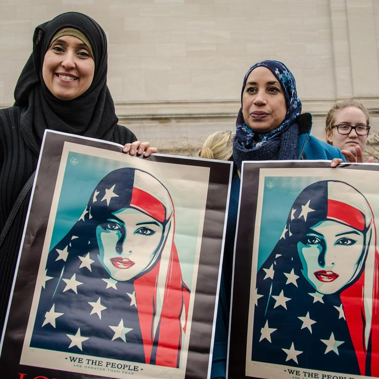 Two muslim women holding up art of Muslim women wearing an American flag over their heads